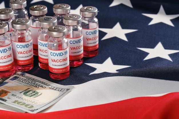 Американский флаг, флаконы с вакциной от коронавируса и деньги