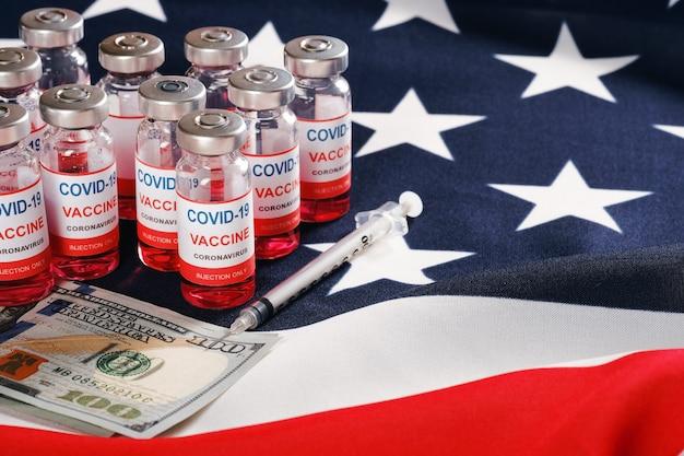 Американский флаг, флаконы с вакциной от коронавируса, шприц и деньги