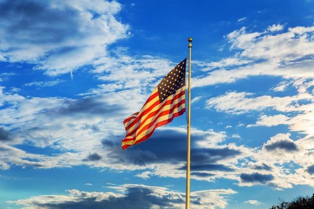 Американский флаг развевается на ветру на фоне голубого неба с белыми облаками