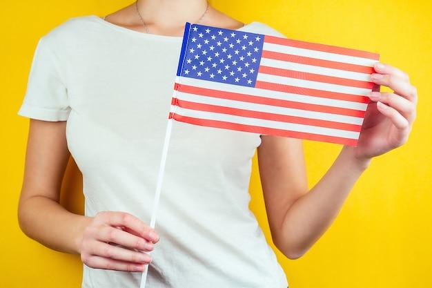 Американский флаг в женских руках с белой футболкой на желтом фоне. концепция дня независимости америки 4 июля.