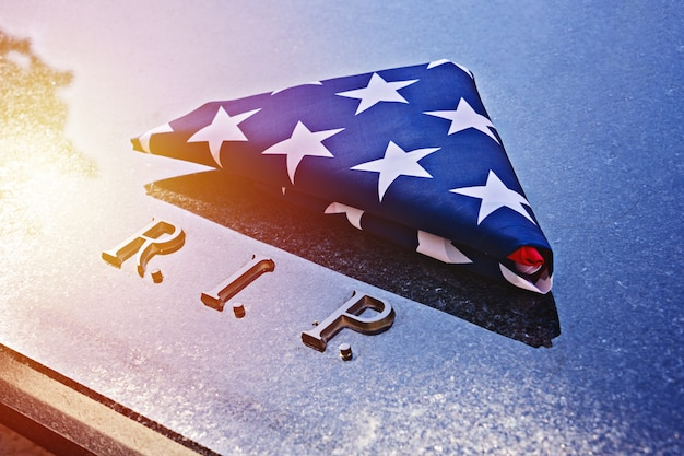 American flag on memorial marble tomb with r.i.p.