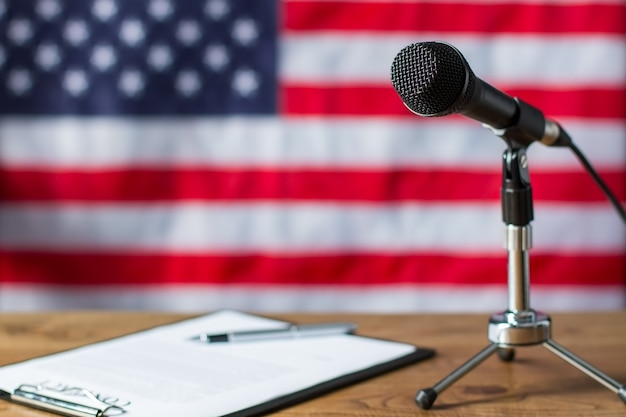 미국 국기, 마이크 및 종이. 배너 옆에 클립보드와 마이크입니다. 테이블에 tv 쇼 시나리오입니다. 뉴스 호스트의 메모.
