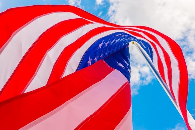 Американский флаг на голубом небе.