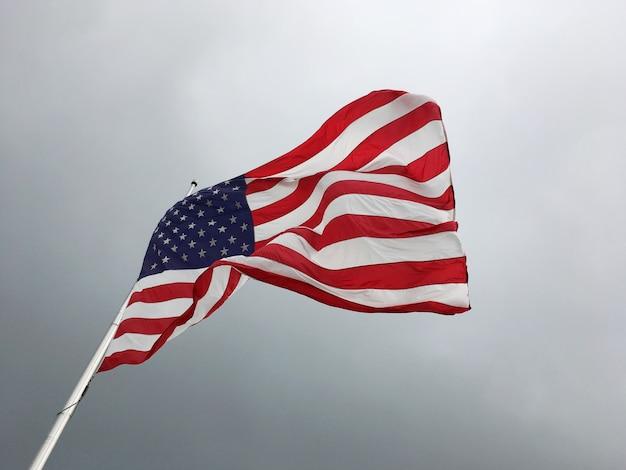 暗い空を背景にアメリカの国旗。半旗を飛んでいるアメリカ合衆国の旗。