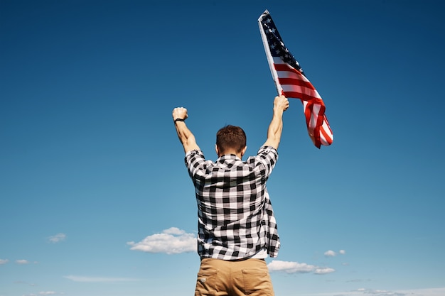 Американский флаг на открытом воздухе мужчина держит национальный флаг сша на фоне голубого облачного неба день независимости 1 июля
