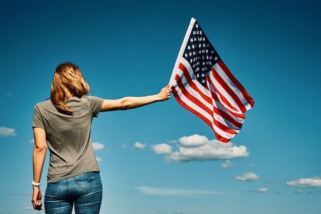Американский флаг на открытом воздухе женщина держит национальный флаг сша на фоне голубого облачного неба день независимости 1 июля