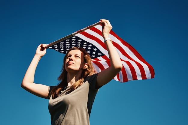Американский флаг на открытом воздухе женщина держит национальный флаг сша на фоне голубого облачного неба