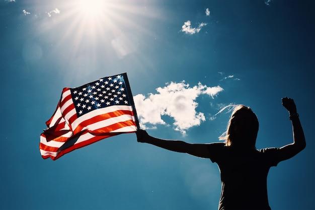 Американский флаг на открытом воздухе силуэт женщины держит национальный флаг сша на фоне голубого облачного неба день независимости 1 июля