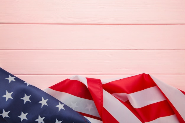 American flag on pink wooden background with copy space