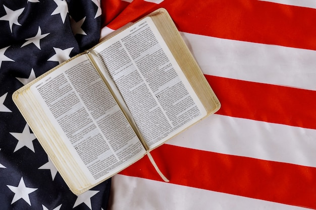 American flag ruffle with open is reading holy bible book with prayer for america over us flag