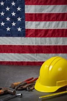 Bandiera americana e strumenti vicino al concetto di festa del lavoro del casco.