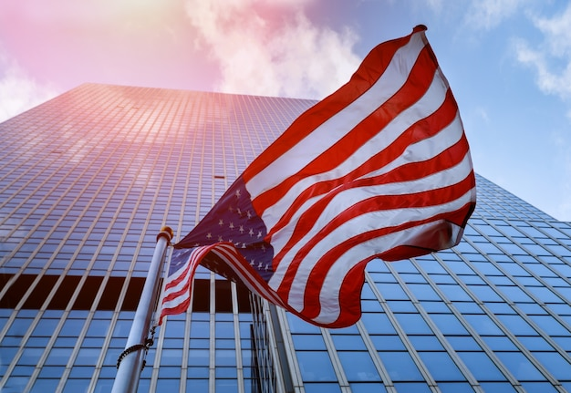 American flag waving against skyscrapers and a blue sky.