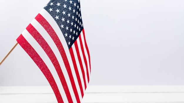 American flag waving against white wall in studio