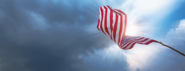 Американский флаг развевается в облачном небе