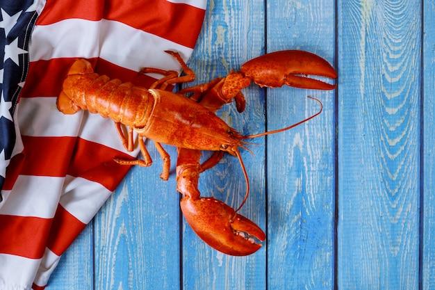 アメリカの休日の夕食のためのおいしいアメリカのロブスターに手を振っているアメリカの国旗