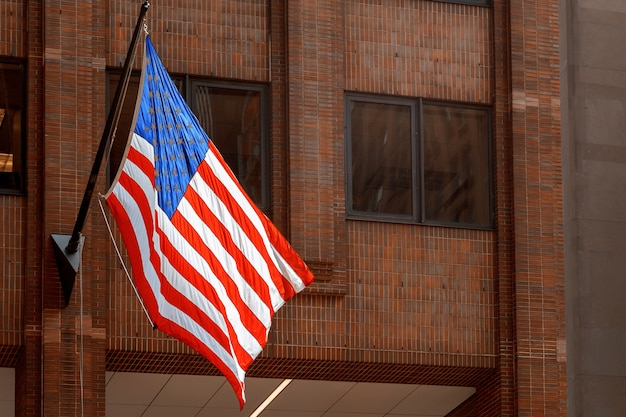 Американский флаг развевается на здании с небоскребами нью-йорк сша
