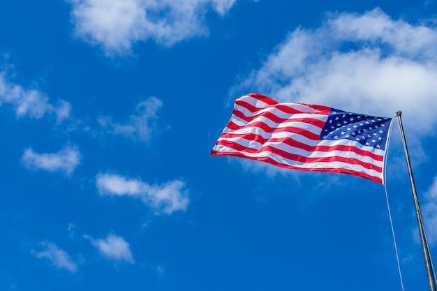 Американский флаг, размахивающий облачным синим небом в солнечный день