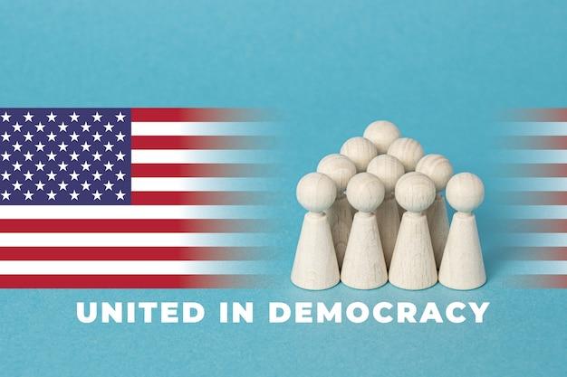 Американский флаг с группой деревянных фигур текст, объединившийся в демократию синий фон