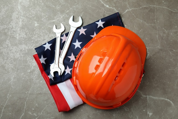 Американский флаг с каской и гаечными ключами на сером текстурированном