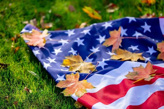 秋の緑の草の上にカエデの葉とアメリカの国旗