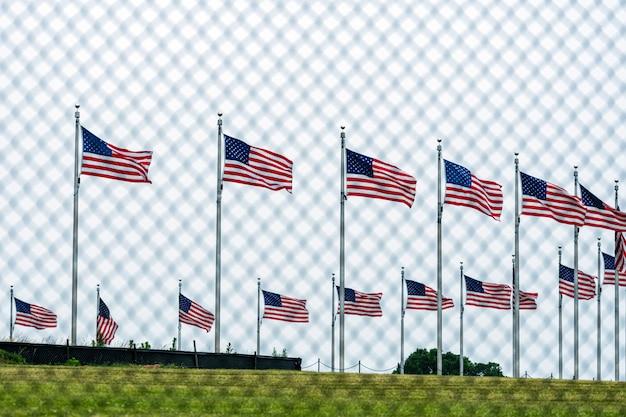Американские флаги на мемориале вашингтона за проволочной изгородью. фокус на флагах