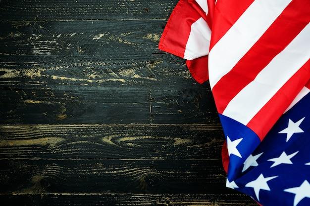 黒い木の背景にアメリカの国旗、7月4日の独立記念日の画像暗い木製の壁のテクスチャの背景にアメリカの国旗。