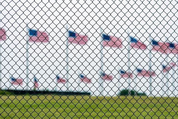 American flags at the washington memorial behind the wire fence. focus on the wire fence