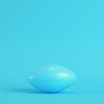 American football ball on bright blue background