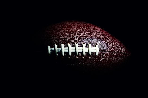 American football ball isolated on black space