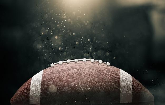 照らされた黒い背景の上のアメリカンフットボールのボール