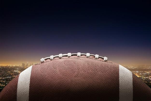 都市の背景にアメリカンフットボールのボール