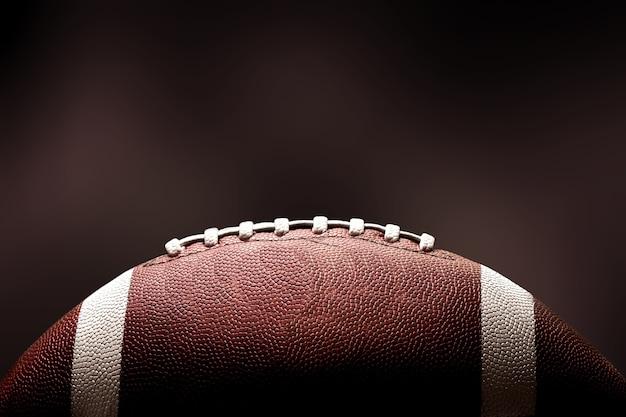 暗い背景のアメリカンフットボールのボール