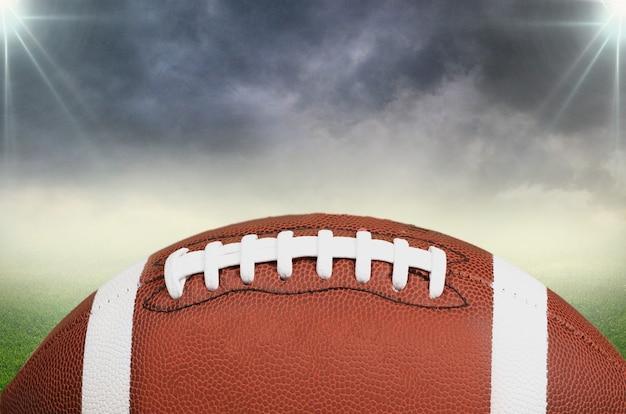 スタジアムフィールドの背景にアメリカンフットボールのボール