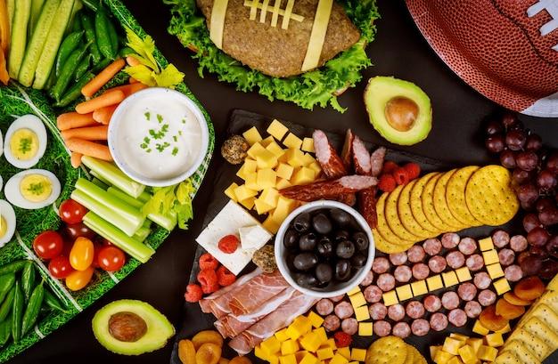 テレビでフットボールの試合を見るために家でパーティーのために食べ物をケータリングするアメリカンフットボールの試合。