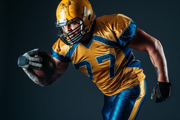 ボールとアメリカンフットボールの攻撃的なプレーヤー