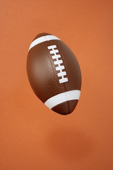 American football on orange background. sport and competition. copy space. 3d illustration