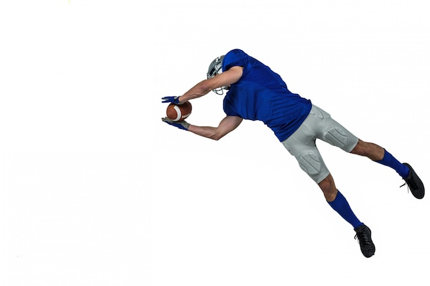 American football player catching ball in mid-air