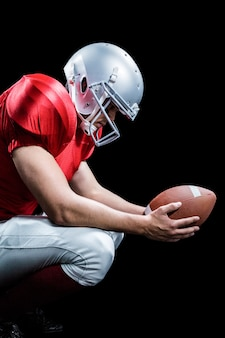 American football player crouching while holding ball