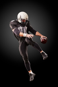 American football player in dark uniform is jumping with the ball on a black surface