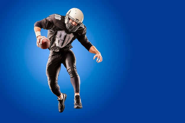 American football player in dark uniform jumping with the ball