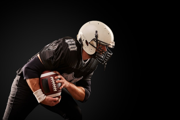 American football player in dark uniform with the ball is preparing to attack on a black wall