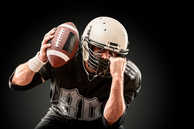 American football player in dark uniform with the ball is preparing to attack