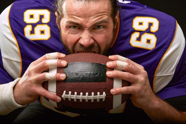 ボールを噛むアメリカンフットボール選手の感情的な顔がクローズアップ