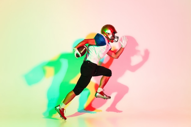 American football player on gradient studio background in neon