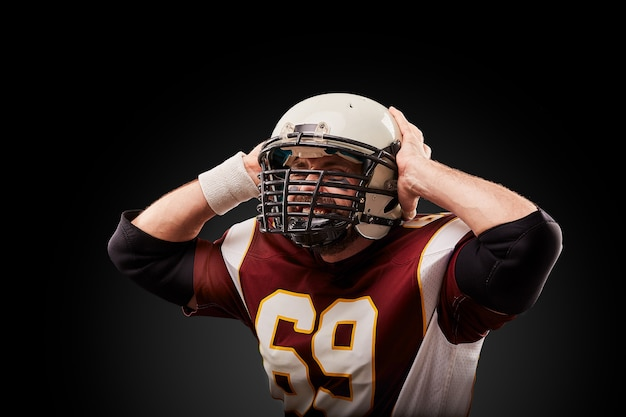 American football player in a helmet holding his head in pain against a black wall