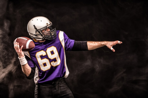 American football player holding ball in his hands in smoke. black background, copy space.