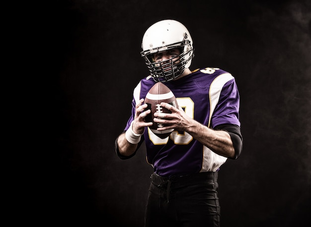 American football player holding the ball in his hands