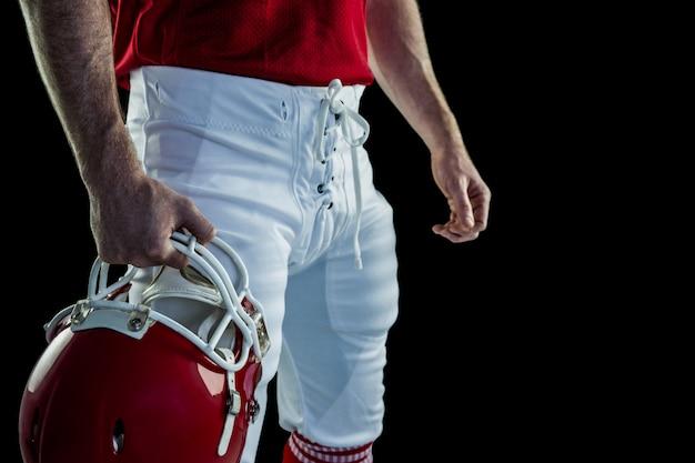 American football player holding his helmet