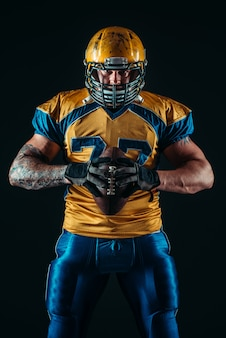 American football player holds ball in hands