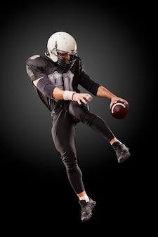 Игрок в американский футбол в темной форме прыгает с мячом на черной поверхности